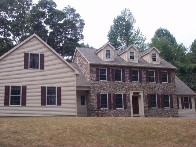 stone and vinyl house with burgundy shutters