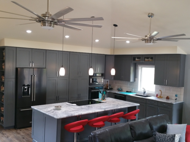 large contemporary kitchen with vaulted ceilings, granite counter tops, and dark grey cabinets