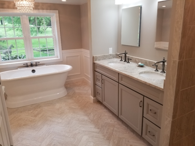 remodeled master bath with cast iron tub, twin windows, and herringbone tile flooring