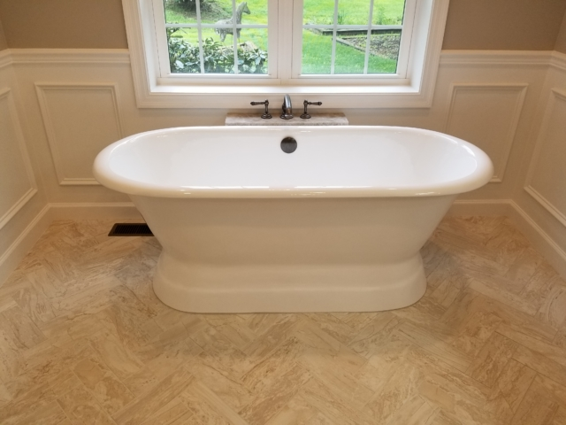 new cast iron tub with twin windows and herringbone tile flooring