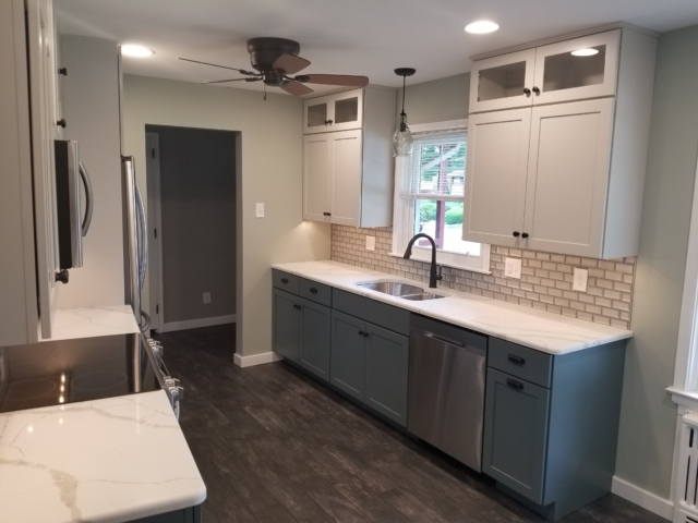 Remodeled kitchen with granite counter tops, stainless steel appliances, and tile backsplash