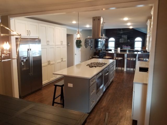 Remodeled kitchen with cooking island, wood flooring, stainless steel refrigerator