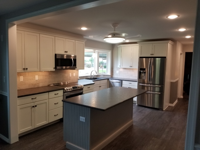 Remodeled kitchen with bay window, vinyl cortex flooring, and tile backsplash