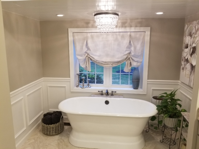 remodeled master bath with a cast iron tub, twin windows, herringbone tile flooring, and raised panel trim