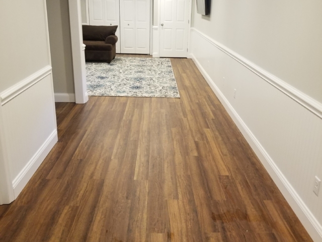 renovated basement with new vinyl flooring and custom trim