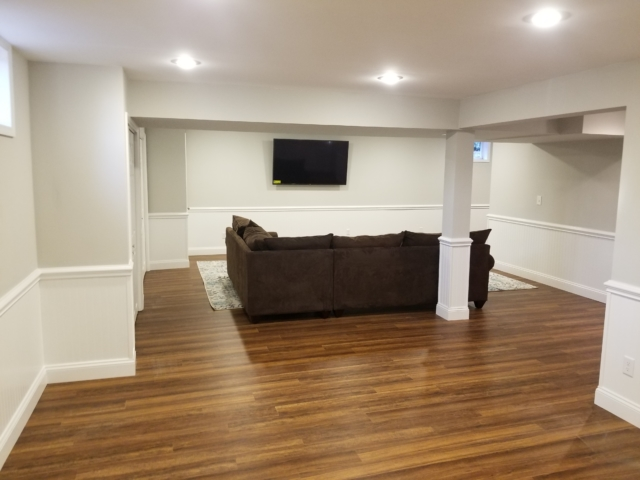 water damaged basement renovation with vinyl flooring, brown couch, and television