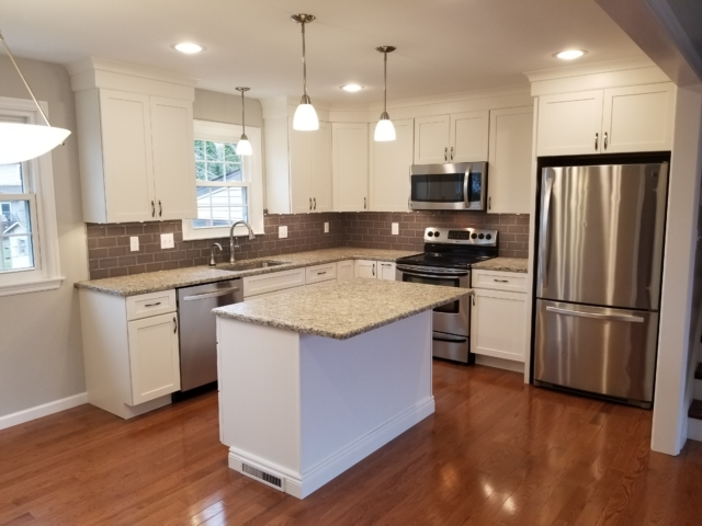 Bright remodeled kitchen with granite counter tops, white cabinets, and stainless steel appliances