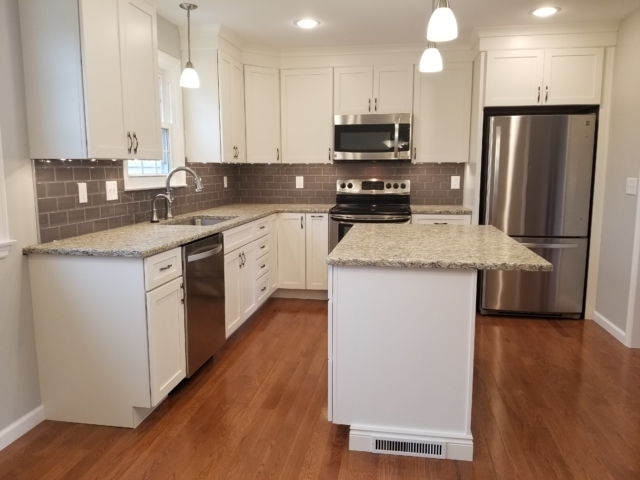 Bright kitchen with granite counters white cabinets and stainless refrigerator