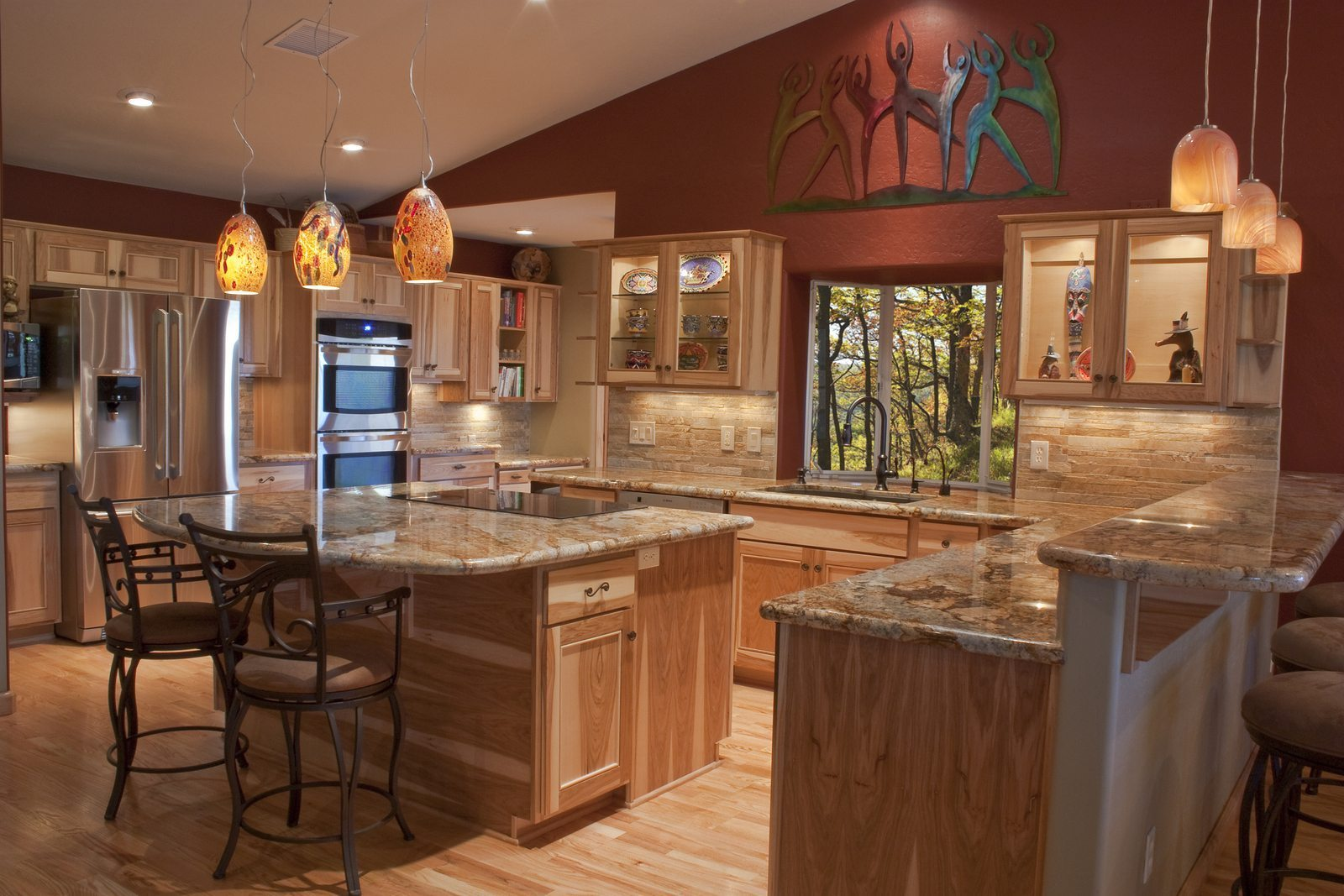 A luxury remodeled kitchen with pendant lights that serve as general lighting and accent lighting
