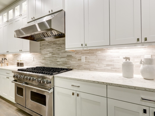 Gourmet kitchen features white shaker cabinets with marble countertops paired with stone subway tile backsplash and stainless steel hood over eight burner gas range. Northwest USA