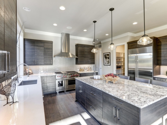 Modern gray kitchen features dark gray flat front cabinets paired with white quartz countertops and a glossy gray linear tile backsplash. Bar style kitchen island with granite counter. Northwest USA
