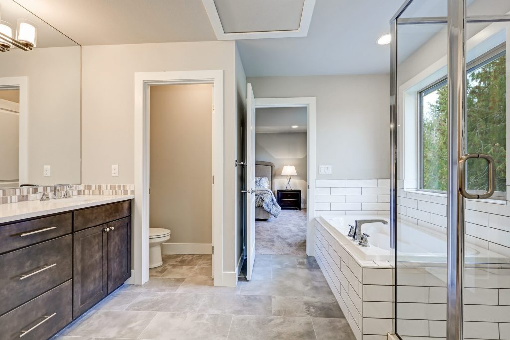 Gorgeous bathroom interior boasts drop-in tub with white tile surround next to glass shower dark wood bathroom vanity accented with mosaic backsplash. Northwest USA