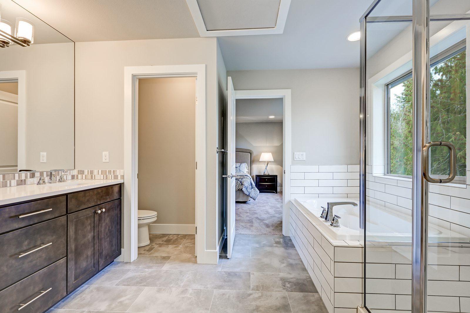 Gorgeous bathroom interior boasts drop-in tub with white tile surround next to glass shower dark wood bathroom vanity accented with mosaic backsplash. Northwest USA