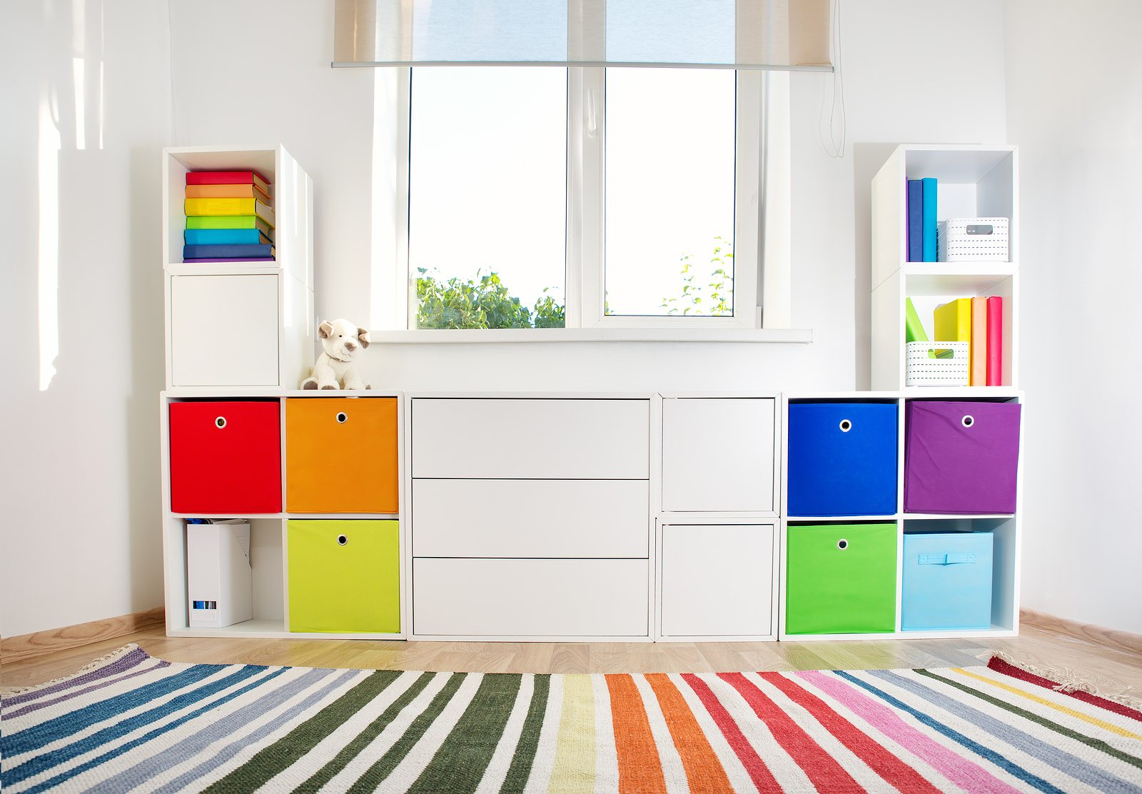 Colourful children rooom with white walls and furniture. Rainbow carpet at home interior with a window