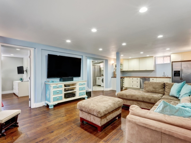 Pastel blue walls in basement living room interior with open floor plan. Large corner sofa with blue pillows and ottoman. Vintage white and blue TV cabinet