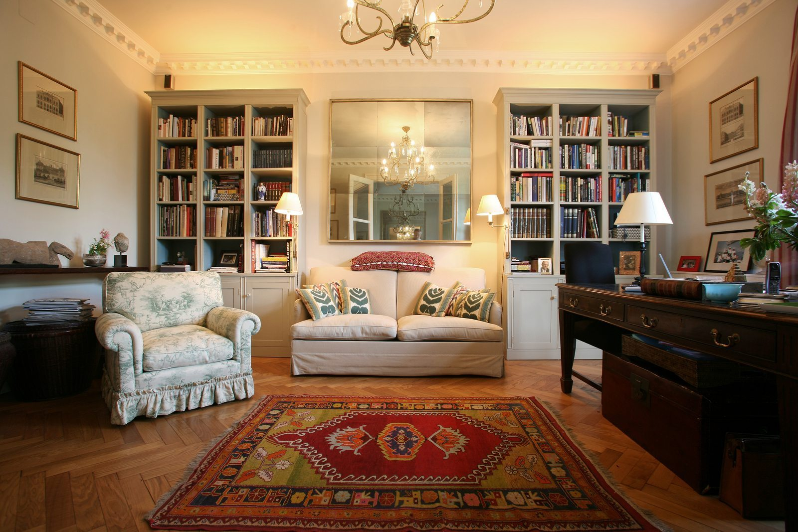 A living room that mixes solid colors and patterns with books and bookshelves in the background