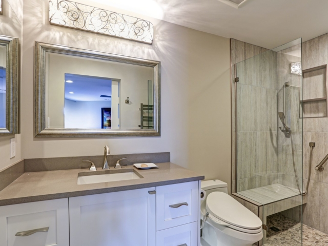 Contemporary bathroom design boasts white bathroom cabinet with taupe Quartz countertop, silver beaded mirror and modern polished chrome faucet lit by decorative lights.