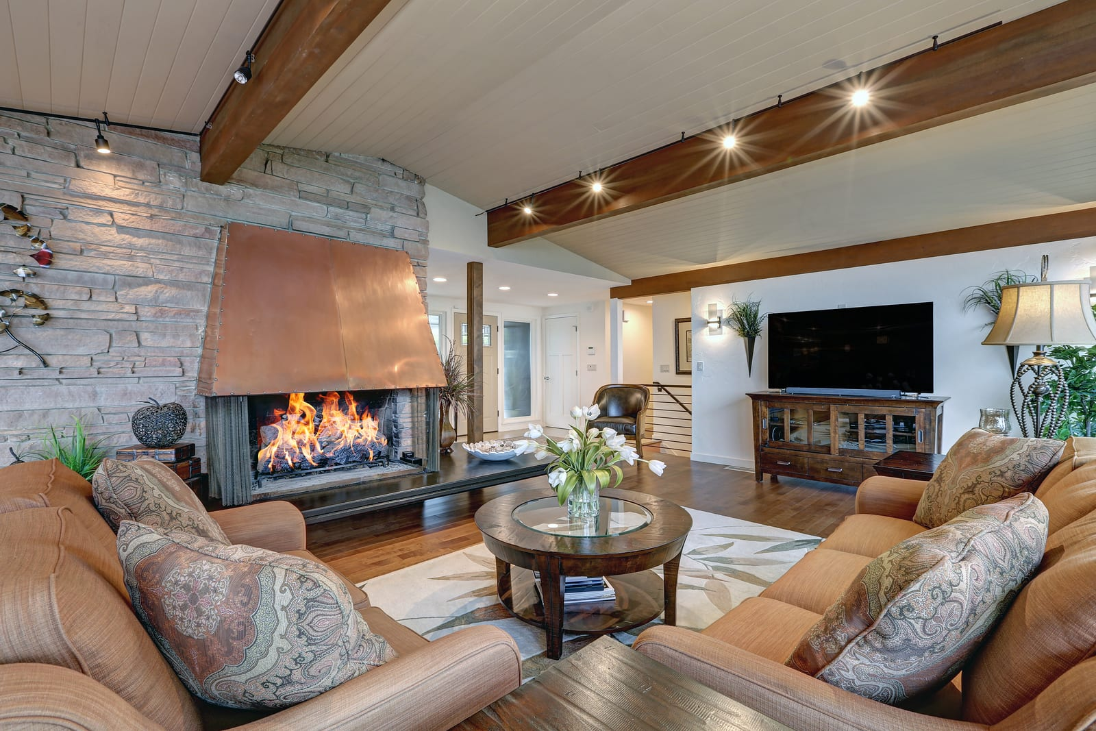 Beautiful panorama house interior features great room with white plank ceiling accented with wood beams over Cozy seating arrangement. Northwest, USA