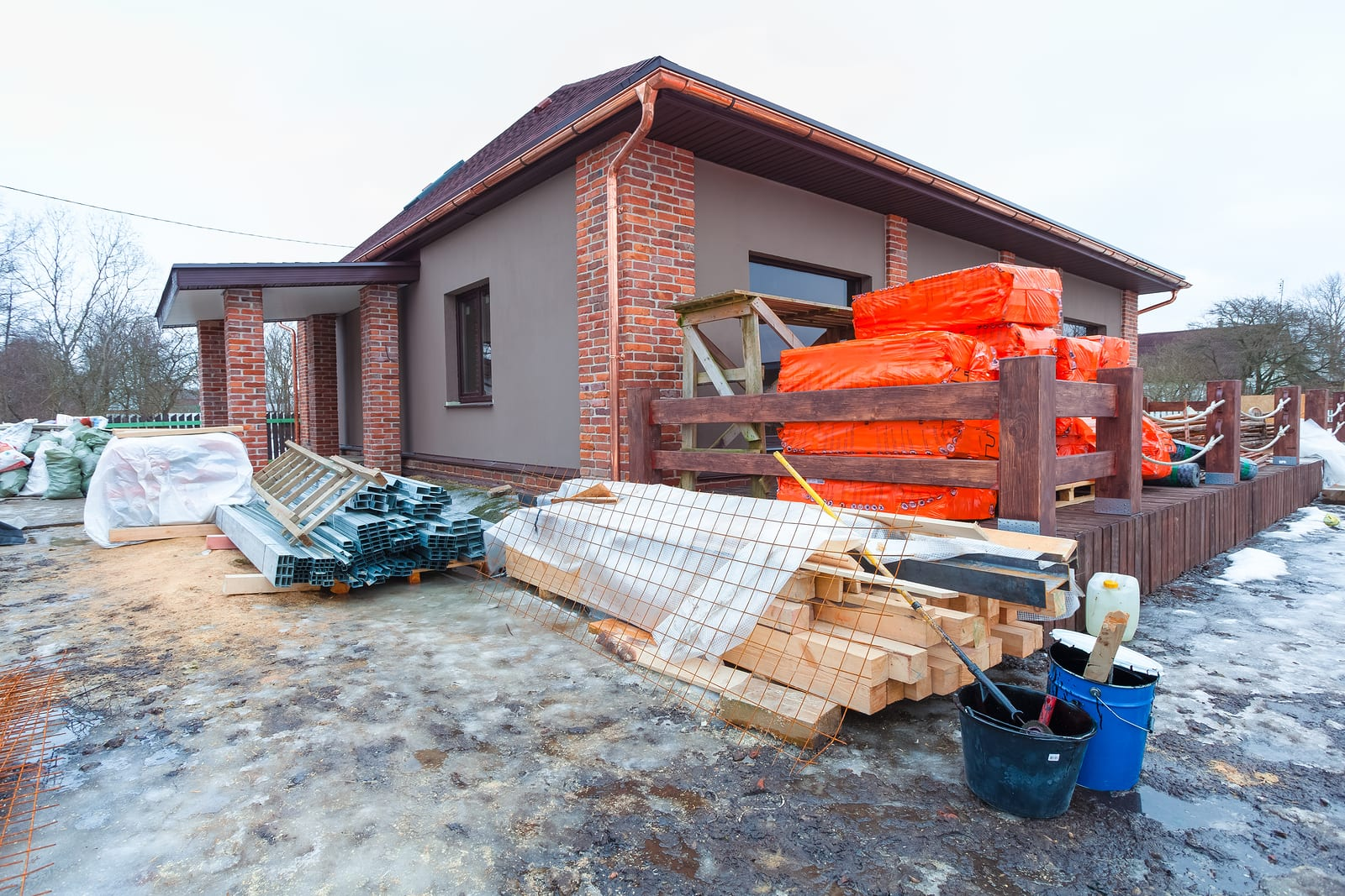 The modern house with terrace is under construction (remodel) and construction material for renovation are outside