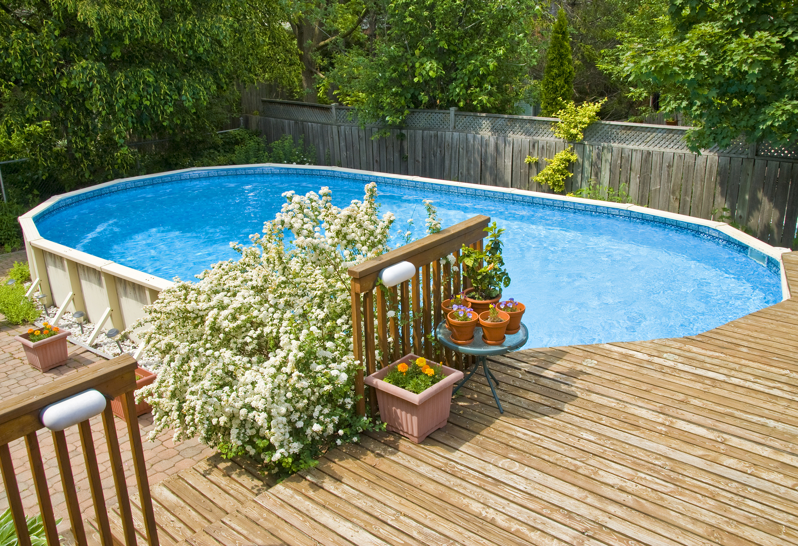 An oval shape above the ground swimming pool and wooden deck.