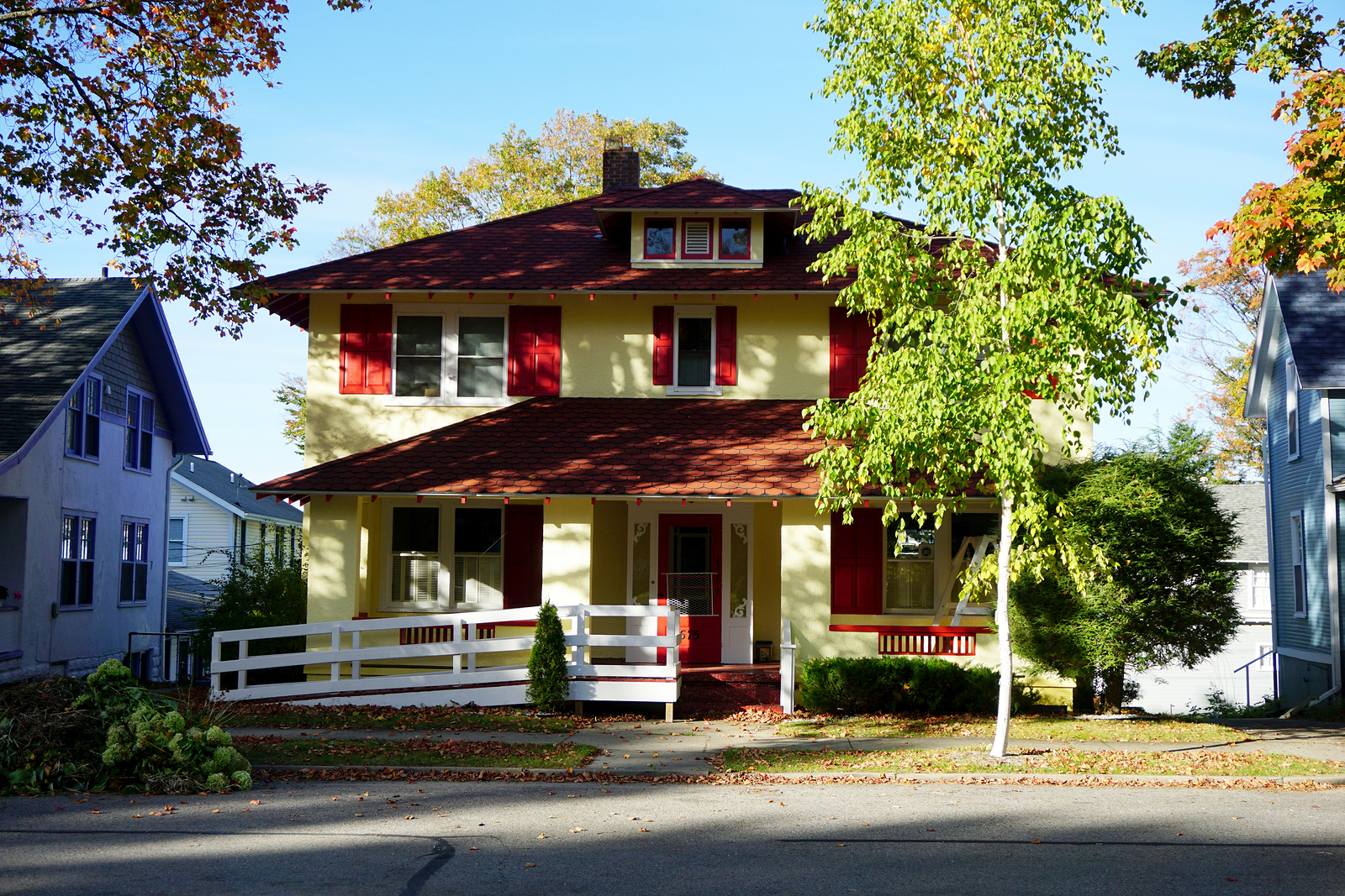 BAY VIEW, MICHIGAN / UNITED STATES - OCTOBER 17, 2017: An elegant yellow stucco summer cottage, with red trim, and a wheelchair ramp, in Bay View.
