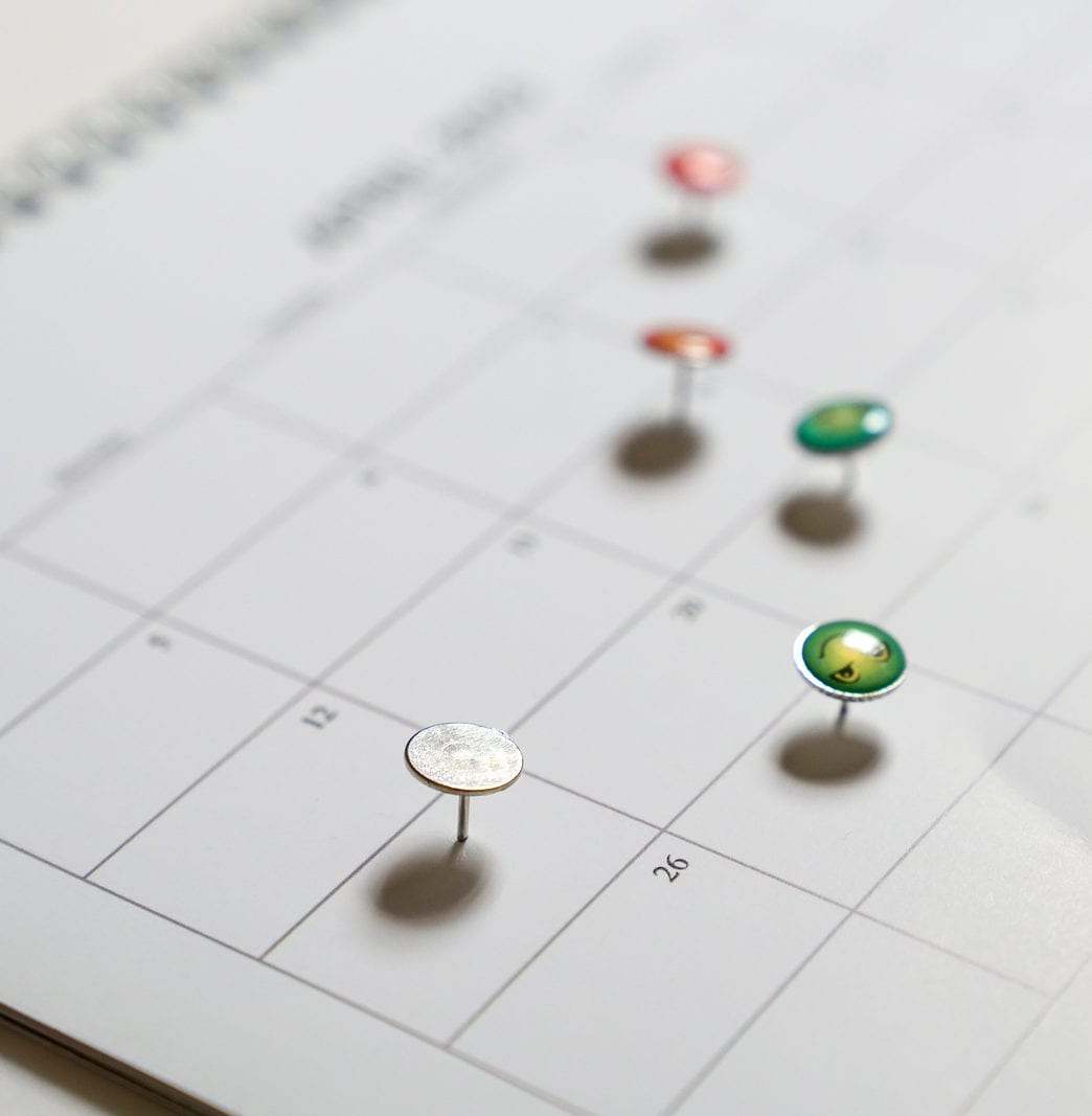 Business concept: thumbtack on calander as reminders for meetings, appointments or deadlines