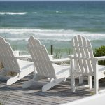 horizontal photograph of wooden deck chairs at the beach