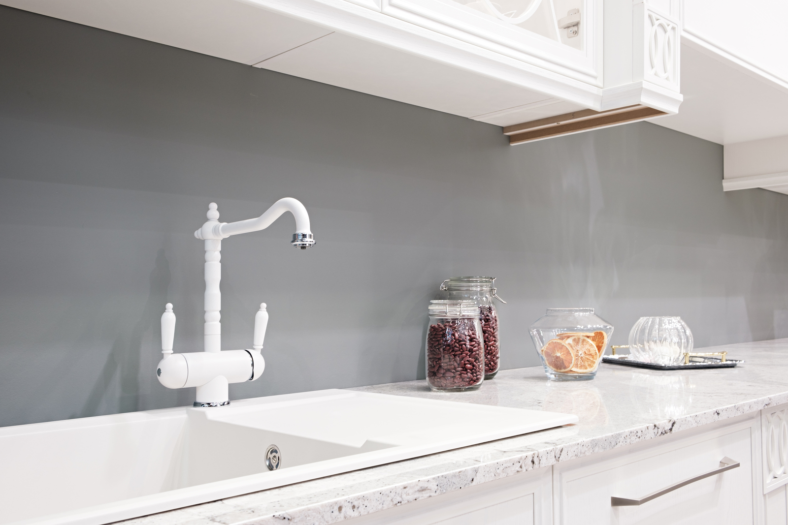 An elegant double-handled faucet in a white sink and countertop looks great and offers excellent temperature control