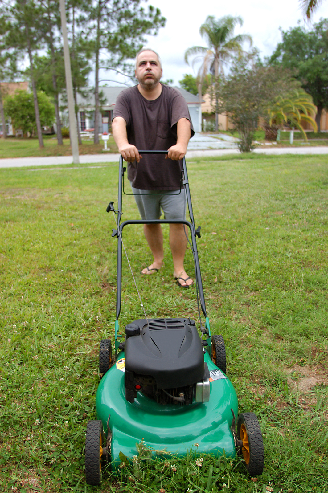 elderly man unhappy about mowing the lawn