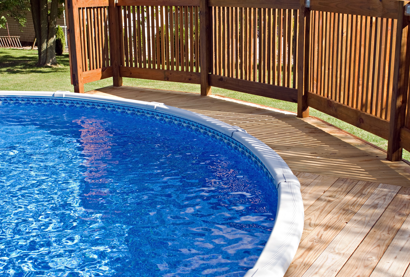 Round above-ground home pool with wooden deck and railing.