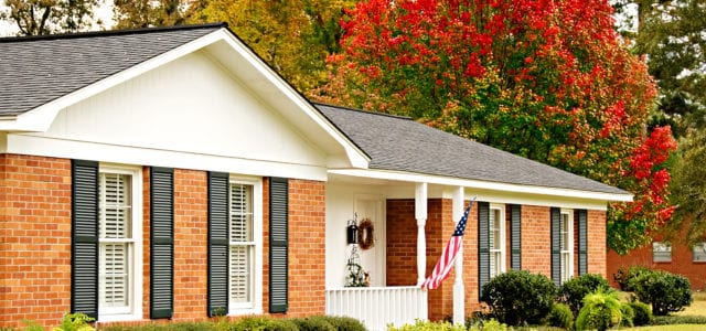 Red brick ranch house adorned with fall color and an american flag.