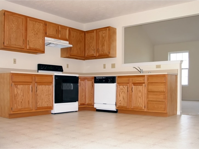 Spacious, bright, clean kitchen in a newly constructed house showing the beautiful oak cabinets and the latest appliances.
