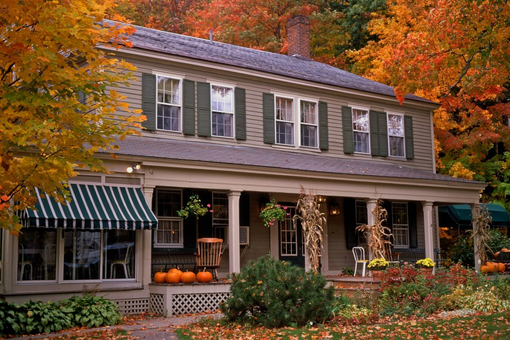 Guest House with orange fall foliage and pumpkins
