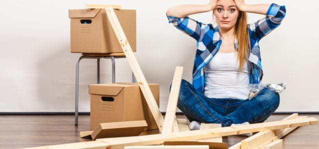 Worried confused woman moving into new apartment house assembling furniture.