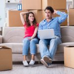Young pair moving in to new house with boxes, concerned about buyers remorse