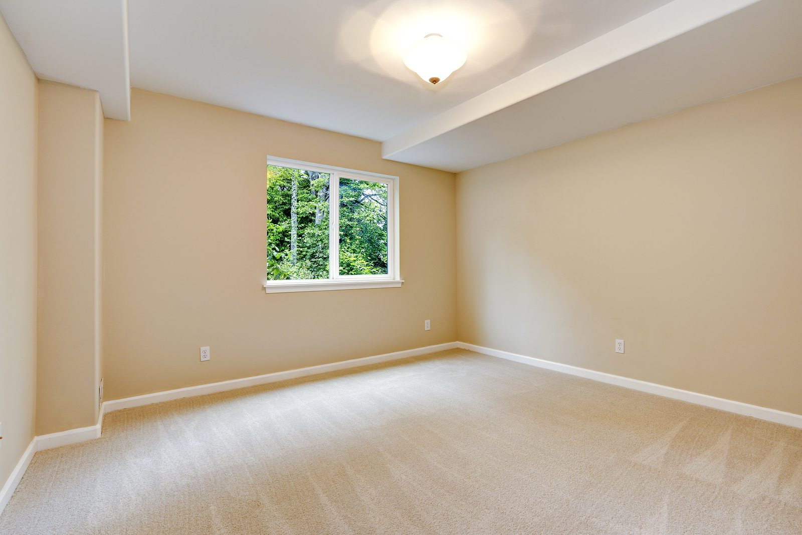 Bright empty bedroom in light ivory tone with carpet floor and small window