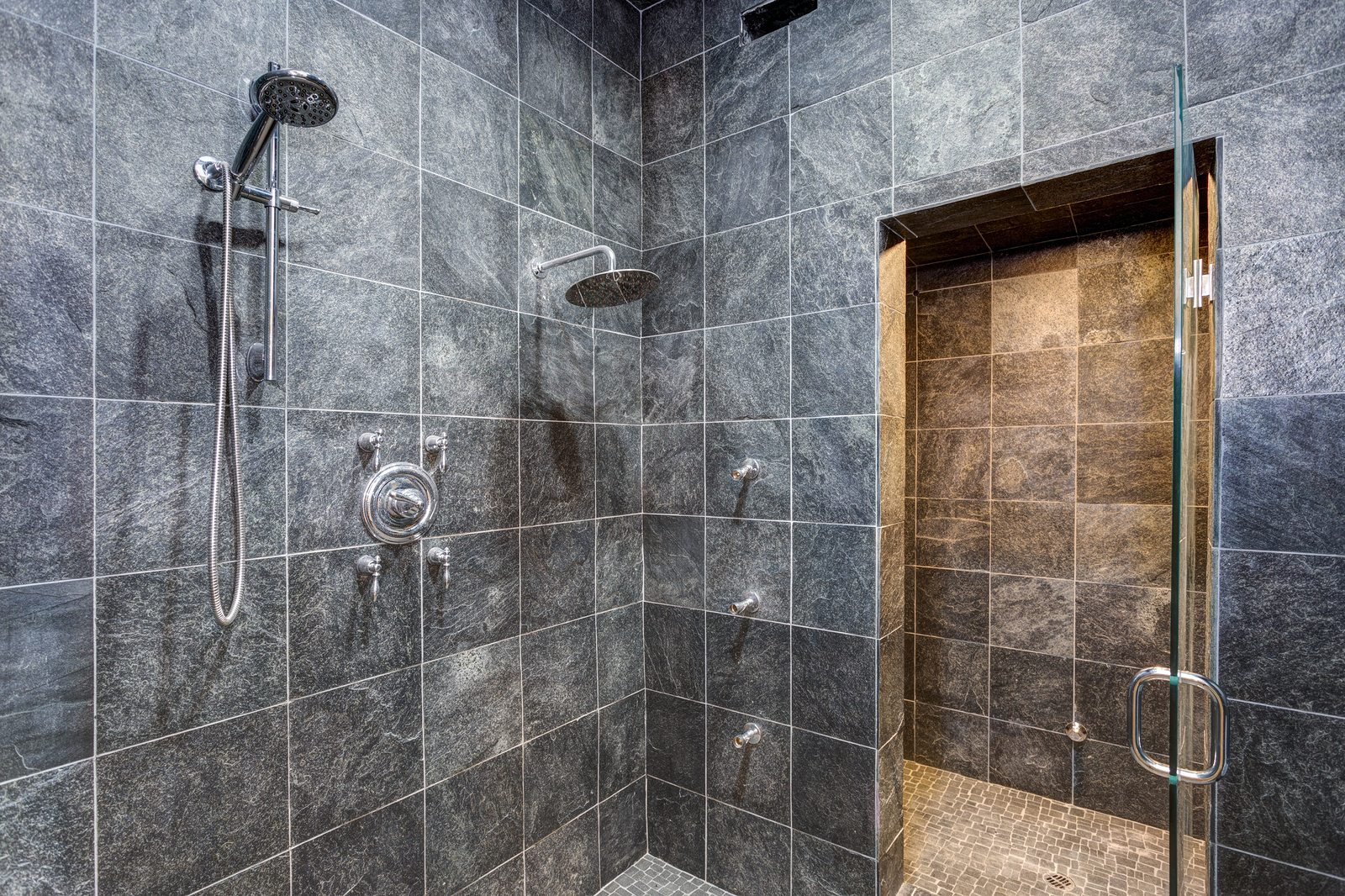 Luxurious mansion wet room style shower with black square tiled walls framing wall mount rainfall shower head.