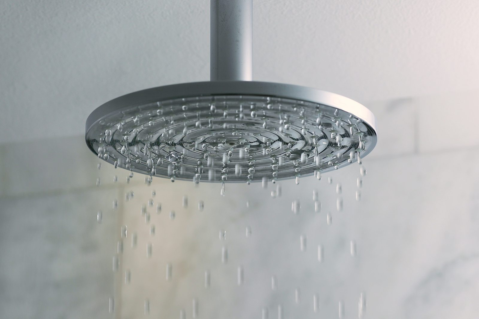Shower turned on, ceiling shower head closeup