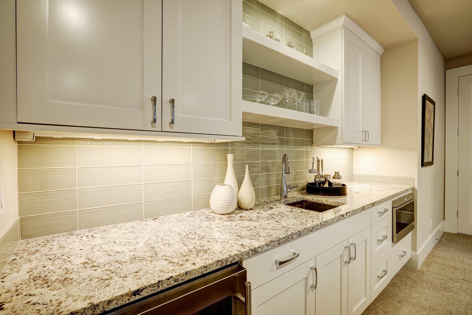 Chic living room features wet bar nook accented with glass subway tiled backsplash white cabinets shelves and granite countertop . Northwest USA
