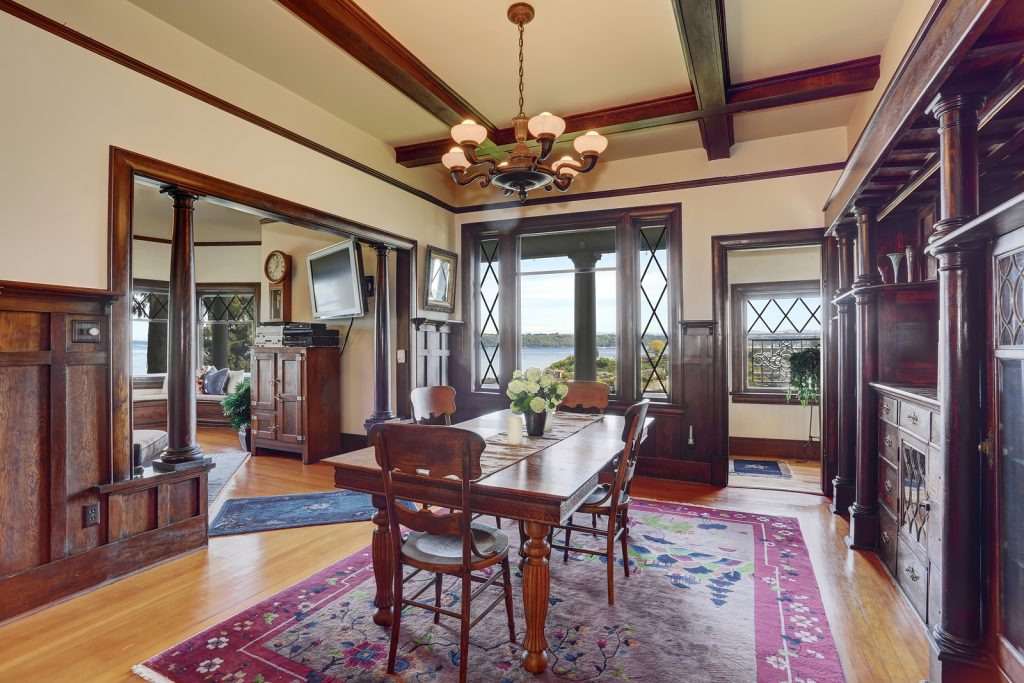 Antique style dining room interior with fresh flowers on the table. Wooden beams ceiling light tones hardwood floor and brown wood trimmed wall
