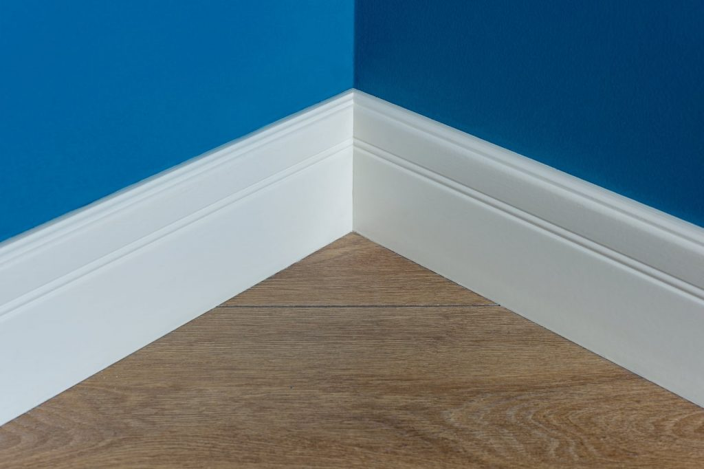 Two baseboards along a floor that meet in the corner of the room