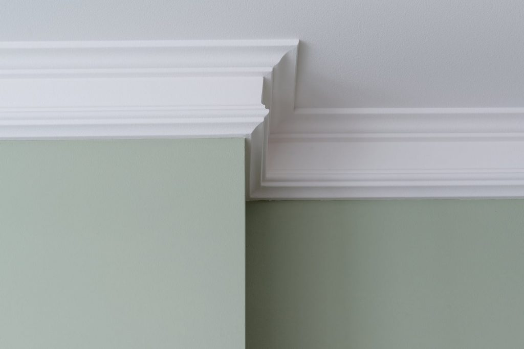 Intricate crown molding along the joint between a wall and a ceiling