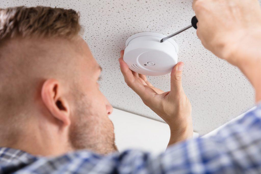 man installing carbon monoxide detector