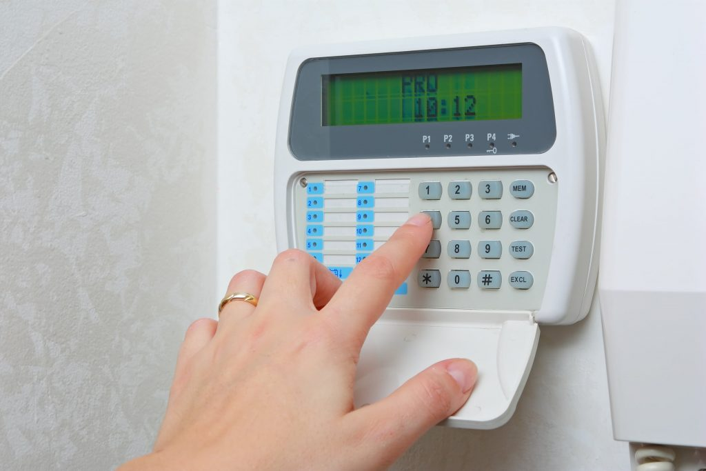 person arming a home security system
