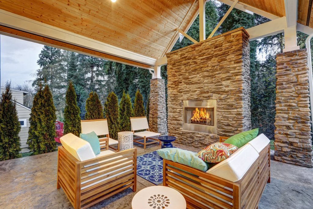 stone outdoor fireplace with comfy seating under a wooden roof
