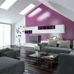 Modern apartment living room interior with a purple accent wall and sloping ceiling with skylights above a parquet floor and modern grey lounge suite with wall cabinets and television