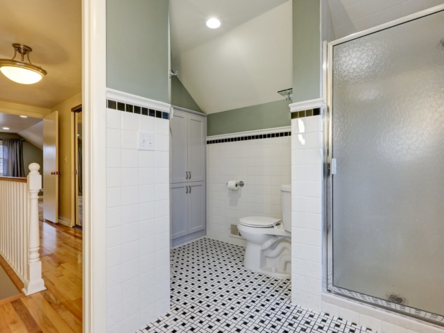 Bathroom features subway tiled half walls with black tile border over vintage black and white tile floor. Northwest USA