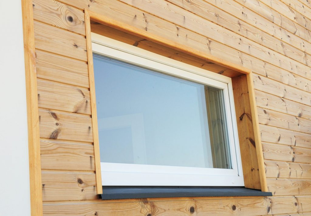 Plastic PVC Window in New Modern Passive Wooden House Facade Wall. PVC Windows are the Number One in House Energy Efficiency.