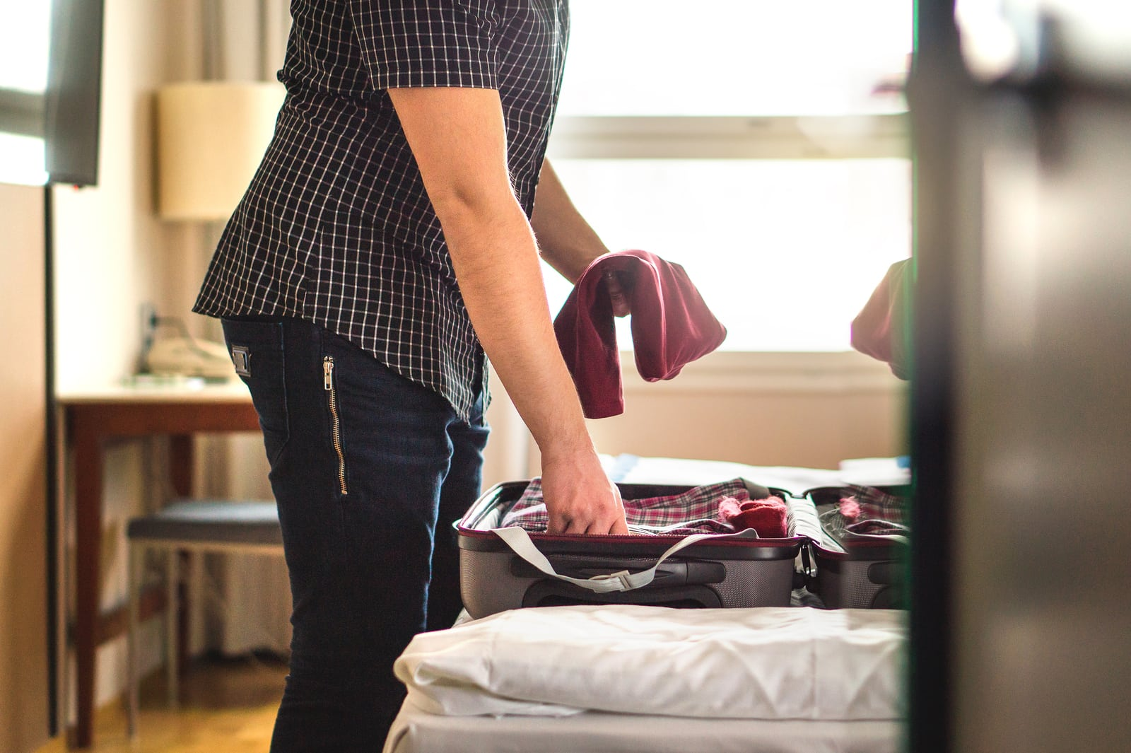 Man packing suitcase for vacation. Person putting clothes to baggagge in hotel room or home bedroom. Traveler with open luggage on bed. Holding t-shirt in hand. Going on or leaving from holiday.
