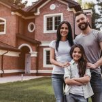 Happy family is standing near their modern house smiling and looking at camera.